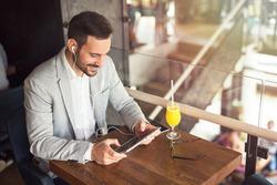 Handsome businessman using tablet at city cafe.