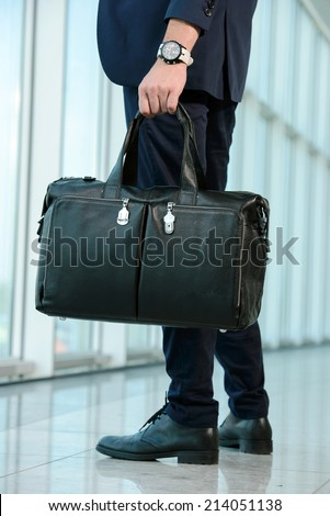 Handsome businessman waiting flight departure time at airport