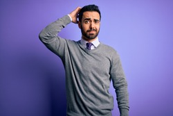 Handsome businessman with beard wearing casual tie standing over purple background confuse and wonder about question. Uncertain with doubt, thinking with hand on head. Pensive concept.
