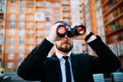 Handsome Businessman with binoculars spying on competitors