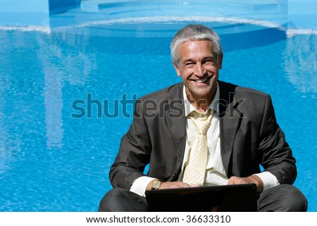Handsome businessman with laptop computer sitting next to swimming pool