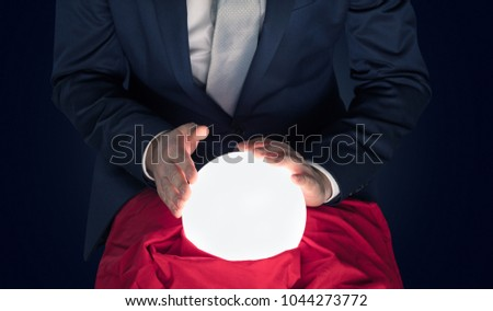 Handsome businessman with magic ball and copy space and dark background #1044273772