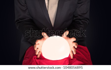 Handsome businessman with magic ball and copy space and dark background #1048056895