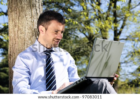 handsome businessman working on laptop in a park