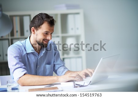 Handsome businessman working with laptop in office
