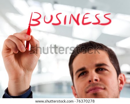 Handsome businessman writing the word business on the screen
