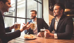 Handsome businessmen are drinking beer, talking and smiling while resting at the pub
