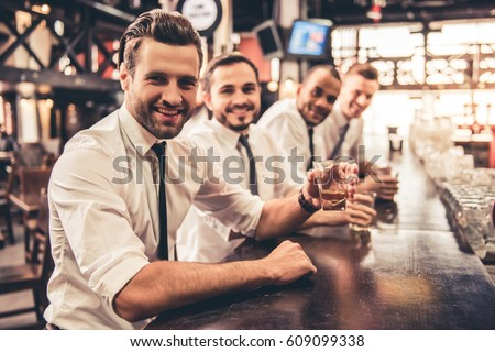 Handsome businessmen are drinking, looking at camera and smiling while resting at the pub