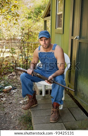 Handsome but threatening-looking man sitting in a plastic chair under a magnolia tree holding the old family shotgun.