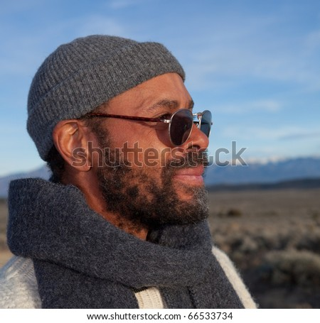 Handsome casual African American man relaxing outdoors in afternoon sun.