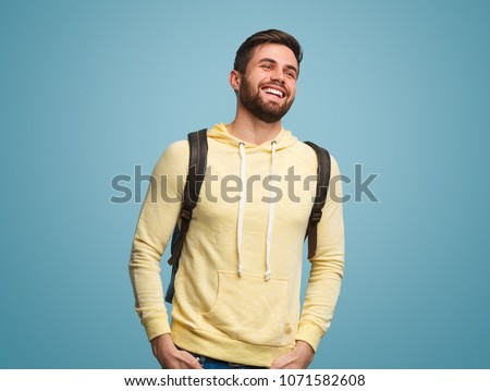 Handsome casual guy with beard wearing backpack and hoodie laughing and looking away on blue.