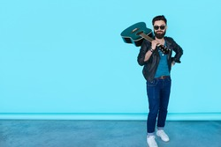 Handsome casual man in black leather jacket with guitar and sunglasses staying in studio isolated on blue background. Full length portrait of guitar player posing against color wall with copy space