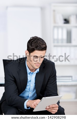 Handsome caucasian businessman sitting in a chair by the office, and working with a tablet
