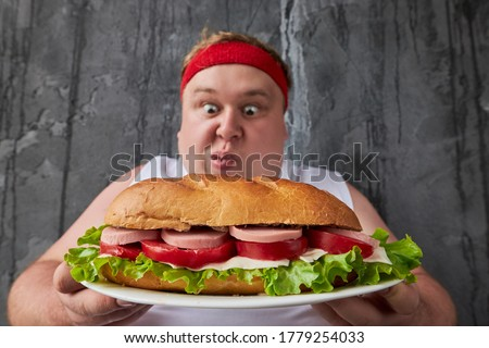 handsome caucasian fat man going to eat big tasty sandwich, he is not embarrassed by his excess weight, he eata what he wants Stock photo ©
