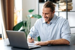 Handsome caucasian guy freelancer uses laptop. Smiling attractive modern man in stylish casual wear sits at the desk in a creative or home office, browsing internet, replies to email, distant learners