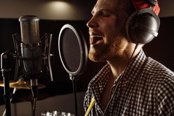handsome caucasian guy in recording studio. young man professional singer preparing before music performance, concert. man warms up the vocal cords