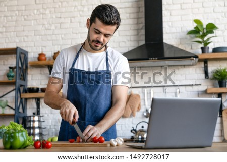 Handsome caucasian man cooking on kitchen with laptop on table #1492728017