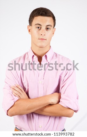 Handsome Caucasian man in a dress shirt, thinking with his arms crossed and looking at the camera with a serious expression