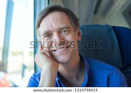 handsome Caucasian man in blue shirt sitting on commuter train in daytime, smiling at camera