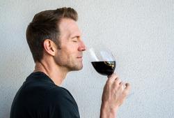 handsome Caucasian man savoring a glass of red wine
