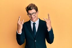Handsome caucasian man wearing business suit and tie shouting with crazy expression doing rock symbol with hands up. music star. heavy concept.