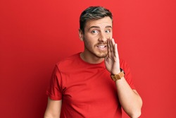 Handsome caucasian man wearing casual red tshirt hand on mouth telling secret rumor, whispering malicious talk conversation