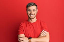 Handsome caucasian man wearing casual red tshirt happy face smiling with crossed arms looking at the camera. positive person.