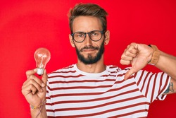 Handsome caucasian man with beard holding lightbulb for inspiration and idea with angry face, negative sign showing dislike with thumbs down, rejection concept