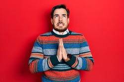 Handsome caucasian man with beard wearing elegant wool winter sweater begging and praying with hands together with hope expression on face very emotional and worried. begging.