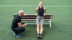 Handsome Caucasian Personal Trainer Wearing Black Clothes and Blue Sneakers, Teaching a Young Beautiful Athletic Girl on a Green Football Field. Gorgeous and Fit Couple Working Out Together.