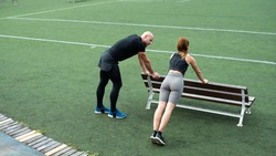 Handsome Caucasian Personal Trainer Wearing Black Clothes and Blue Sneakers, Training a Young Beautiful Athletic Girl on a Green Football Field. Gorgeous and Fit Couple Working Out Together.