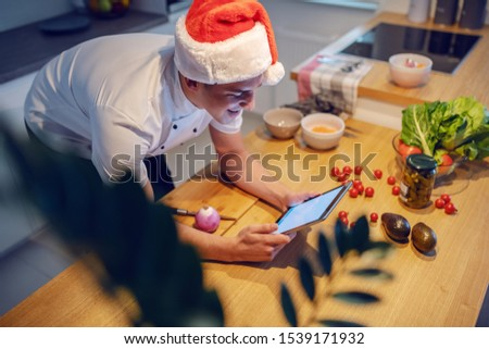 Handsome caucasian smiling chef in white uniform and with santa hat on head using tablet while leaning on kitchen counter. On kitchen counter are cherry tomatoes, avocado, spices and onion.