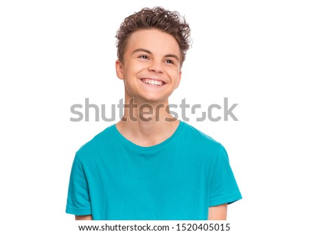 Handsome caucasian Teen Boy in blue t-shirt, isolated on white background. Teenager looking away and smiling. Happy child - close-up portrait.