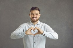 Handsome caucasian young man expresses a gesture of love while standing on a gray background. Smiling man in front of the camera shows his heart with his hands. Concept of romance and human emotions.