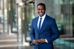 Handsome charming cheerful african american businessman in swanky modern stylish suit and tie, colorful, classy, office building