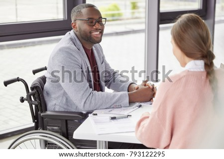 Handsome cheerful black male invalid in wheelchair involved in charity, meets with female investor, discuss main details, helps physically challenged people. People, health and business concept
