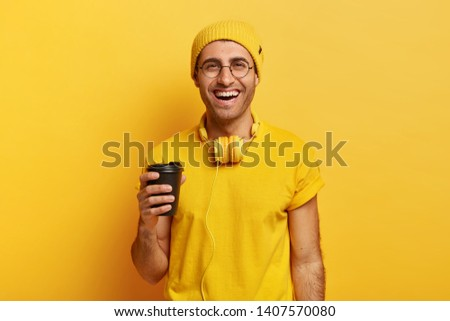 Handsome cheerful man uses headphones holds takeaway coffee, being in good mood, wears stylish yellow headgear and t shirt, has fun while enjoys aromatic drink, poses in studio. Monochrome shot