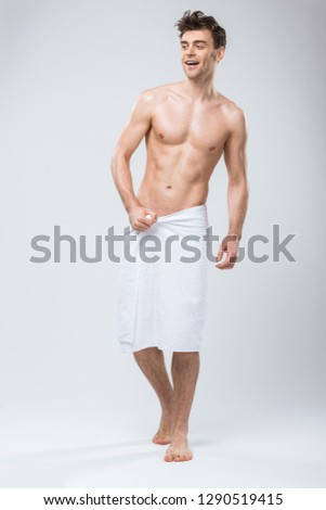 handsome cheerful shirtless man posing in towel isolated on grey