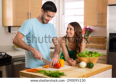 Handsome chef man and beautiful woman on a date chopping vegetables and a nutritious meal and salad