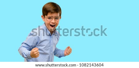 Handsome child with green eyes happy and excited celebrating victory expressing big success, power, energy and positive emotions. Celebrates new job joyful over blue background