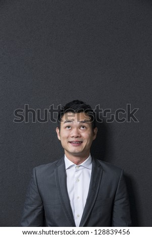 Handsome Chinese business man looking up. Standing in front of a black wall. The photo has been composed so there is plenty of space for a message or text.