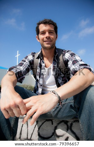 Handsome christian man wearing casual clothes, smiling in front of a modern church.