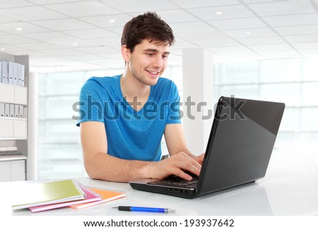 Handsome college student using his laptop computer in the campus