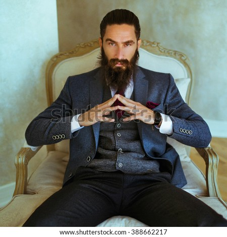 Handsome confident bearded man sitting in luxury white chair
