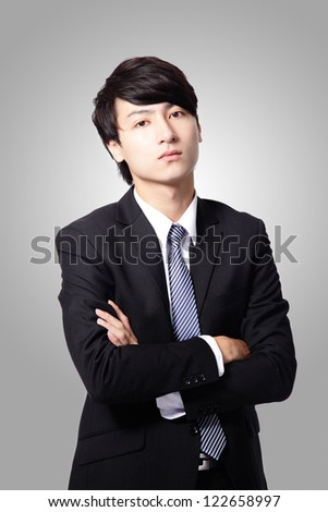 handsome confident business man cross his arms in suit posing isolated on gray background, asian male model