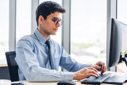 Handsome confident businessman relaxing looking at technology of desktop computer monitor while sitting on chair.Young creative coworkers business people working and typing on keyboard at office