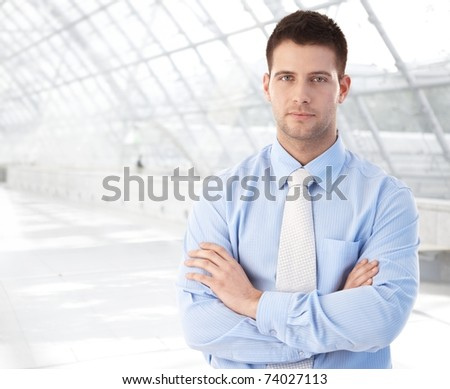 Handsome confident businessman standing at modern office lobby arms crossed.?