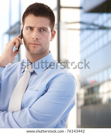 Handsome confident businessman talking on mobile phone in business quarter.?