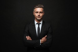 Handsome confident businessman wearing suit standing isolated over black background, arms folded