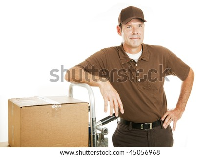 Handsome, confident delivery man or mover leaning on his dolly.  Isolated on white.